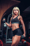Woman doing exercises with dumbbell in the gym Stock Images