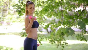 Woman Doing Exercises With Dumbbell In The Park stock footage