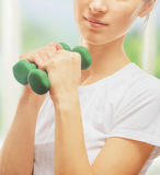 Woman is doing exercises with dumbbells Stock Photography