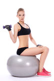 Woman doing exercises with dumbells. Beautiful woman doing exercises with dumbells on fitness ball over white background Royalty Free Stock Photo