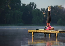 Woman doing exercises in nature on the river stock photography