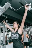 Woman doing exercises on a pull-up machine. Sports women doing exercises on a pull-up machine power training apparatus in the gym royalty free stock images