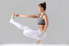 Woman doing Extended Hand to Big Toe pose with squat. Young attractive woman practicing yoga, doing Toe Balance, variation of Extended Hand to Big Toe pose with stock photo