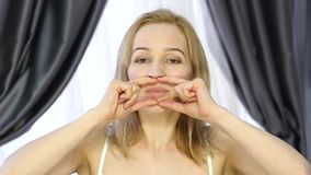 Woman doing face fitness, aging chang in the muscles of the face. strengthening of the upper and lower eyelid.  stock footage