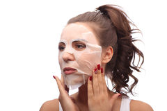 Woman doing facial mask sheet. Beauty and Skin Care Concept. Girl applying facial mask. Brunette women doing facial mask sheet. Beauty and Skin Care Concept Stock Photos