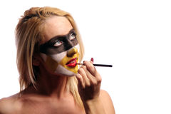 Woman doing fashion make-up. Beautiful blonde woman doing fashion make-up, isolated on white, may be use like pilferer concept Stock Photo