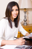 Woman doing finances. A woman doing finances at her desk and smiling Royalty Free Stock Photography