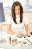 Woman doing financial calculation. Attractive young woman doing financial calculation at home, using calculator, counting money stock image