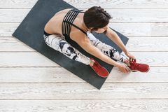 Woman doing fit exercise on white flooring Stock Images