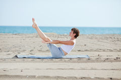 Woman doing fitness exercise on beach Stock Photo