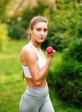 Woman doing fitness exercises with dumbbells in summer park Stock Images