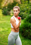 Woman doing fitness exercises with dumbbells in summer park Stock Photography