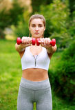 Woman doing fitness exercises with dumbbells in summer park Royalty Free Stock Image