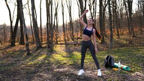 Woman doing fitness exercises outdoor. Female runner stretching before running marathon in green forest. Slim girl in