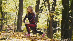 Woman doing fitness exercises outdoor. Female stretching in autumn forest. Slim girl at outdoor workout stock video