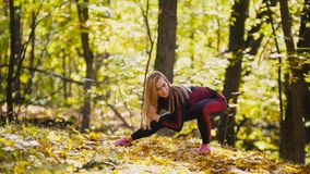 Woman doing fitness exercises outdoor. Female stretching in autumn forest. Slim girl at  workout - squats. Woman doing fitness exercises outdoor. Female Stock Image