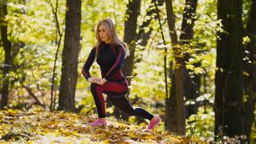 Woman doing fitness exercises outdoor. Female stretching in autumn forest. Slim girl at  workout. Woman doing fitness exercises outdoor. Female stretching in Stock Photo