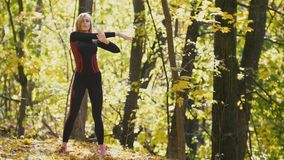 Woman doing fitness exercises outdoor. Female stretching her arms in autumn forest. Slim girl at outdoor workout stock video