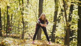 Woman doing fitness exercises outdoor. Female stretching her loin in autumn forest. Slim girl at outdoor workout stock video