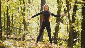 Woman doing fitness exercises outdoor. Female stretching her shoulders in autumn forest. Slim girl at outdoor workout stock video footage