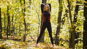 Woman doing fitness exercises outdoor. Female stretching her shoulders in autumn forest. Slim girl at  workout Royalty Free Stock Photo