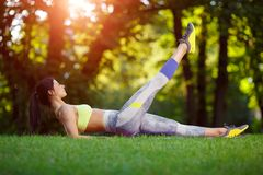 Woman doing fitness exercises in the park royalty free stock image
