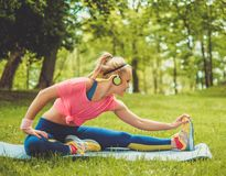 Woman doing fitness exercises. Sporty woman doing fitness exercises outdoors Royalty Free Stock Photos