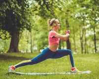 Woman doing fitness exercises. Sporty woman doing fitness exercises outdoors Stock Image
