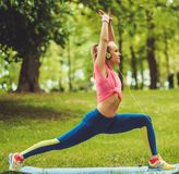 Woman doing fitness exercises. Sporty woman doing fitness exercises outdoors Stock Photography