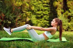 Woman doing fitness exercises in summer park, workout outdoors. Woman doing fitness exercises in a summer park, workout outdoors Stock Photos