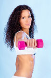 Woman doing fitness exercises. Young woman with long curled hair doing fitness exercises Stock Image
