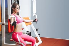 Woman doing fitness training on a butterfly machine with weights in gym or fitness club stock photos