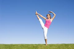 Woman doing Fitness and Yoga. A beautiful young woman outdoors stretching and preparing for Yoga and exercise Stock Photography