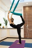 Woman doing fly yoga stretching standing on one leg on the ground and second in hammock. Fit and wellness lifestyle royalty free stock photo