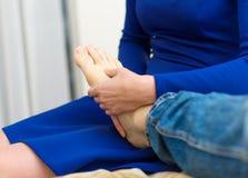 Woman doing foot massage. Stock Photos