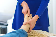 Woman doing foot massage. Royalty Free Stock Photography