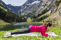 Woman doing forearm plank pose outdoors Stock Photos