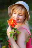 Woman doing garden work sniffing at the rose Royalty Free Stock Image