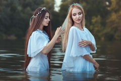 Woman doing hairstyle girlfriend. Woman takes care of the hair of her girlfriend, they in nature or standing in water royalty free stock photo