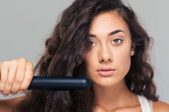 Woman doing hairstyle with hair straightener Stock Image