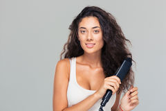 Woman doing hairstyle with hair straightener Stock Images