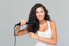 Woman doing hairstyle with hair straightener Royalty Free Stock Images