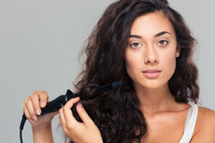 Woman doing hairstyle with hair straightener Stock Photos