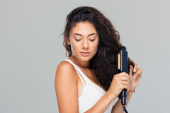 Woman doing hairstyle with hair straightener Royalty Free Stock Photo