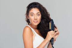 Woman doing hairstyle with hair straightener Stock Photography