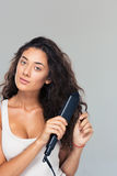 Woman doing hairstyle with hair straightener Stock Photo