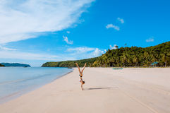 Woman doing handstand on beach Stock Photography