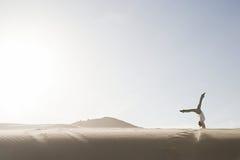 Woman doing handstand in desert Stock Images