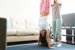Woman Doing Handstand While Friend Assisting Her During Pajama P. Young women doing handstand while friend assisting her during pajama party at home stock image
