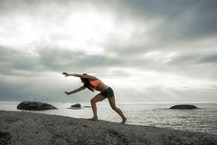 Woman doing a handstand on a rock at sunset on Bakovern Beach, Cape Town. royalty free stock photo